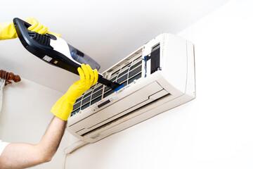 掃除機の吸い込み口をエアコン内部にあて、ホコリを吸い取っている様子