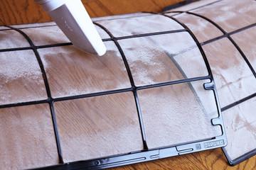 掃除機の吸い込み口を取り外したフィルターの表面にあて、フィルター表面のホコリを吸っている写真